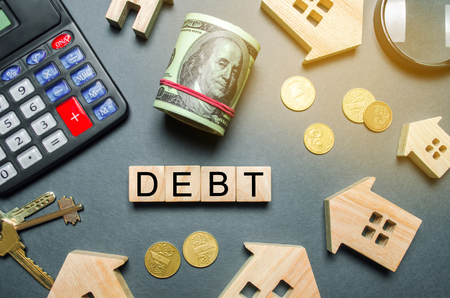 Wooden houses, a calculator, keys, coins and blocks with the word Debt. The concept of debt for housing. Mortgage Real estate. Loans property concept. Payment of debt. Calculating interest for a house Stock Photo