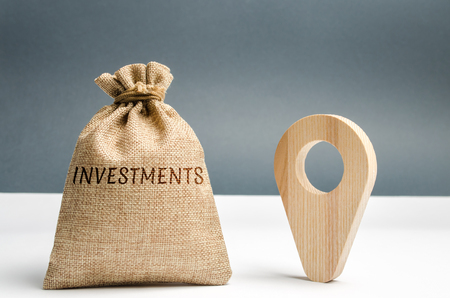 Money bag with the word Investments and a geolocation marker. Point and direct investments in a region or country. Construction of new factories and infrastructure. Economic attractiveness Stock Photo - 118036206