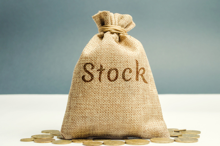 Money bag with the word Stock and coins. Trading on the stock exchange. Investment portfolio. Capital gains. Common and preferred stocks. Market trading and pricing. Share price determination.
