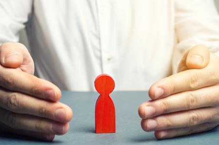El agente de seguros protege la figura del hombre rojo. El concepto de apoyo y cuidado. Ayuda psicológica. Orientación sobre el camino correcto. Trabaja con el personal. Seguros de personas. Contratación y búsqueda de talento.