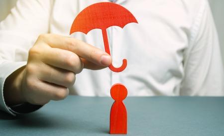 Un agente assicurativo tiene un ombrello rosso su una figura umana. Concetto di assicurazione sulla vita e sulla salute. Reddito incondizionato. Tutela dei diritti. Sicurezza. Assistenza legale. Paracadute d'oro Archivio Fotografico