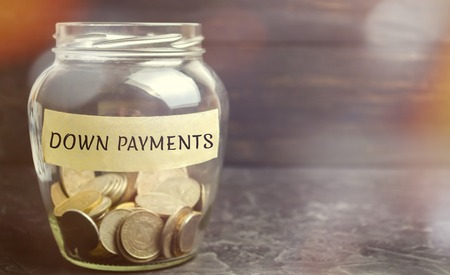 Glass jar with the word down payments. Payment used in the context of the purchase of expensive items such as a car and a house, whereby the payment is the initial upfront portion of the total amount