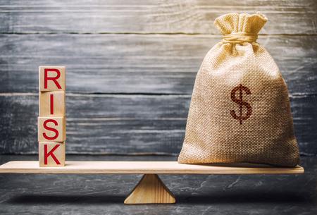 Borsa dei soldi e blocchi di legno con la parola rischio. Il concetto di rischio finanziario. Rischi giustificati. Investire in un progetto imprenditoriale. Prendere la decisione giusta. Assicurazione sulla proprietà. Rischi legali e di mercato