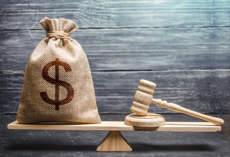 Borsa di soldi con il simbolo del dollaro e il martello di un giudice sulla bilancia. Concetto di lobbying per l'adozione di una legge o di una norma, corruzione. Pagamento di multe e sanzioni. concessione del risarcimento del danno