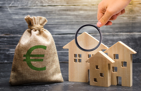 Magnifying glass is looking at a bag with euro money and three houses. Affordable cheap loan, mortgage. Taxes, rental income. Building houses. Concept of real estate acquisition and investment.