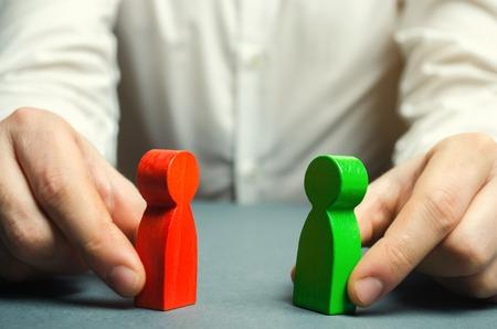 Un uomo tiene tra le mani le figure rosse e verdi di persone che si fronteggiano. Risoluzione dei conflitti, conflitto di interessi. La ricerca di un compromesso, la mediazione nelle trattative. Intrecciare intrighi. Archivio Fotografico