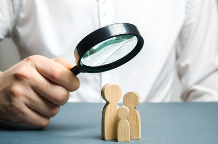 A man looks through a magnifying glass at a family figure. The study of family composition and demographic situation. Statistical data. The program of support for young families, financial assistance. 版權商用圖片 - 118036423