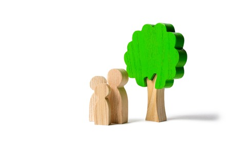 Family figures are standing near the tree on an isolated background. Pastime with family, kinship and parenting. Instilling good qualities and values in a healthy society. The concept of happiness