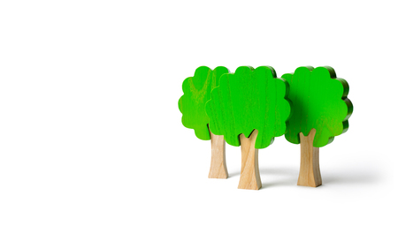 Three toy wooden figures of trees on an isolated background. Forest imitation. environmental conservation. Light planets. Family tree, a symbol of strength and wisdom. Illegal deforestation.