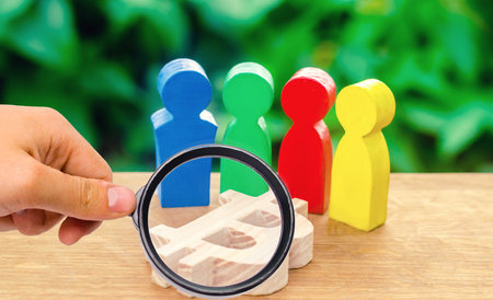 magnifying glass is looking at Four multi-colored figures of people surround a bitcoin figure. Conceptual conduct of activities around cryptocurrency and blockchain technology. Selective focus 写真素材