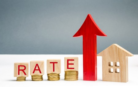 Wooden blocks with the word Rate, up arrow and wooden house. The concept of raising interest rates on mortgages. Growing interest on the loan. Rates are a type of property tax system Stock Photo