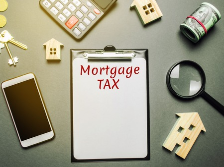 Table with wooden houses, calculator, coins, magnifying glass with the word Mortgage Tax. Property taxes. Calculation of interest on housing tax. Penalty, arrears. Register of taxpayers for property
