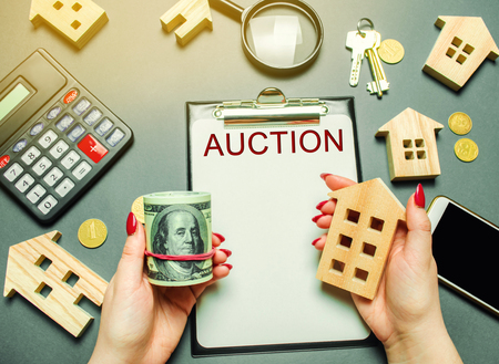 Table with the word Auction. The women auctioneer is holding money in the hands of dollars and a wooden house. Purchase and public sale of real estate. Sell or buy a house  apartment