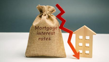 Zak met het geld en het woord hypotheekrentetarieven en pijl naar beneden en huis. Lage rente in hypotheken. Het verlagen van de rentelasten voor hypotheken. De daling van de huizenprijzen op krediet. Lage vraag naar woningen Stockfoto