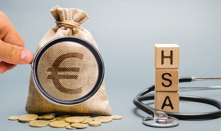 Wooden blocks with the word HSA and money bag with stethoscope. Health savings account. Health care. Health insurance. Investments. Tax-free medical expenses. Coins and euro sign