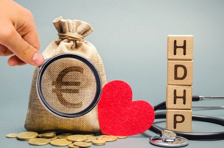 Wooden blocks with the word HDHP and money bag with euro sign. High-deductible health plan concept. Health insurance plan with lower premiums and higher deductibles than a traditional health plan Reklamní fotografie