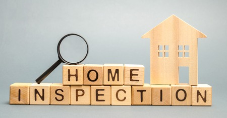 Wooden blocks with the word Home Inspection and the house. Resale residential property condition. The study of the state of the house associated with the sale of housing. Property valuation