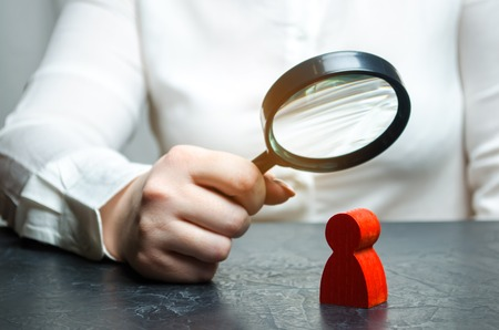 Business woman examines a red man's figure through a magnifying glass. Analysis of the personal qualities of the employee. Characteristic. Unreliable employee. Toxicity in the staff of workers