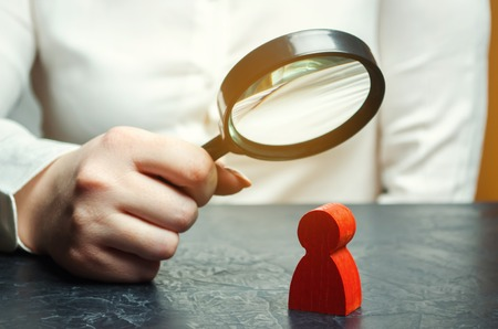 Business woman examines a red mans figure through a magnifying glass. Analysis of the personal qualities of the employee. Characteristic. Unreliable employee. Toxicity in the staff of workers