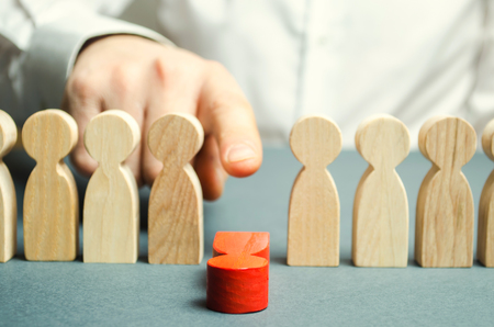 The boss dismisses the employee from the team. Personnel Management. Bad worker. Demotion. Weak link. Team Management concept. Resignation. Male hand is pushing a red man