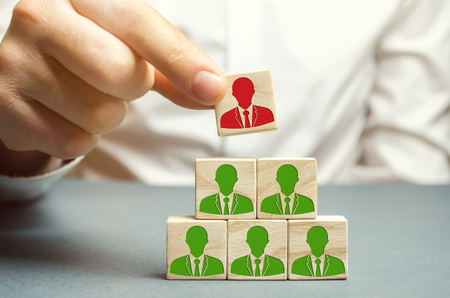 The boss dismisses the employee from the team. Personnel Management. Bad worker. Demotion. Weak link. Team Management concept. Resignation. A man removes a cube with the image of a man. Stock Photo - 118835237