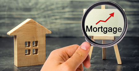 Wooden house and the inscription Mortgage and up arrow. Raising mortgage rates and tax. The increase in interest charges. Reduced demand for housing. Loan for housing, apartment and property.
