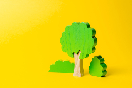 Wooden figures of trees and bushes on an orange background. Preserving the environment from human influence. Illegal deforestation. Restoration of natural habitats The concept of forests and nature.