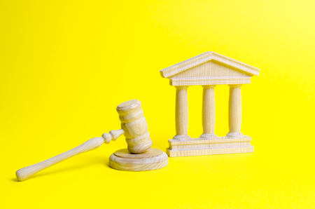 Wooden judge hammer and government building on a yellow background. Court. Concept of the state judicial system. Prohibitions and criminalization, repression, restriction of freedoms and rights