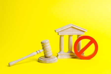 Wooden judge hammer and government building on a yellow background. Court. Concept of the state judicial system. Laws and the constitution, lack of Supremacy of rights and freedoms