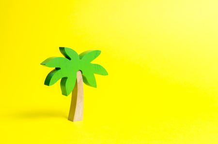 Wooden palm tree on an yellow background. Conceptual leisure and vacation, entertainment and relaxation. Tours and cruises to warm countries. The development of tourism. Tropical island. Stok Fotoğraf