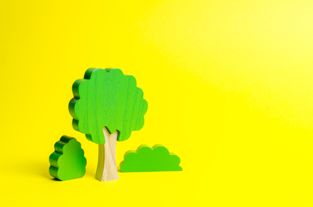 Wooden figures of trees and bushes on an yellow background. The concept of forests and nature. Preserving the environment from human influence. Illegal deforestation. Restoration of natural habitats