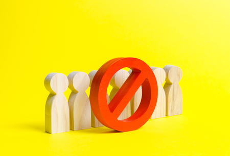 People figurines stand behind the red NO symbol on a yellow background. The concept of a ban on the expression of other opinions, suppression of dissent and freedom of speech. Genocide, repression.