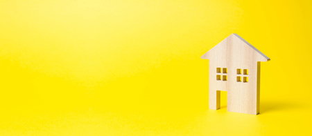 Wooden residential house on a yellow background. Mortgage and credit for the purchase. Minimalism. Isolate Real estate concept, buying affordable housing, real estate renting. Property tax. Banner 写真素材