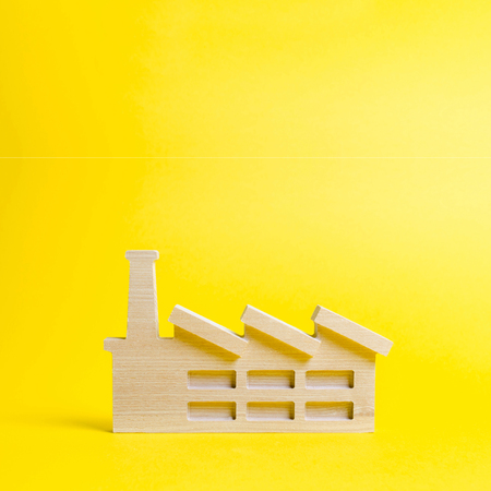 Wooden figurine of a plant or factory on a yellow background. Recycling raw materials. The concept of industry and production.Investments in the construction of new factories.