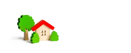 Wooden hut and tree figurines with bushes on an isolated background. The concept of a love nest. Acquisition of affordable housing in a mortgage or loan. Accommodation for families. Banner