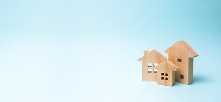 Wooden houses on a blue background. Wooden Toys. The concept of real estate and ownership, purchase of property. Farm, city, village, enterprise. Construction and improvement of buildings. banner Stock Photo