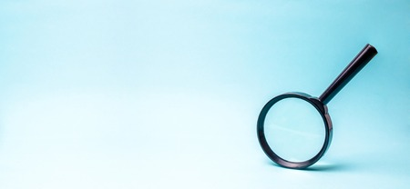 Lupa sobre fondo azul. búsqueda y análisis, analítica y estudio de detalles. Validación, identificación de falsificaciones y delitos, revisión y estudio del mundo. bandera Foto de archivo
