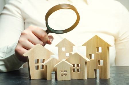 A woman is holding a magnifying glass over a wooden houses. Real estate appraiser. Property valuation / appraisal. Find a house. Search for housing. Real estate market analysis. Selective focus