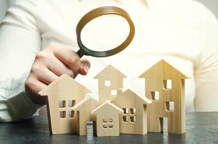 Een vrouw houdt een vergrootglas over houten huizen. Vastgoedbeoordelaar. Taxatie / taxatie van onroerend goed. Zoek een huis. Huisvesting zoeken. Analyse van de vastgoedmarkt. Selectieve focus