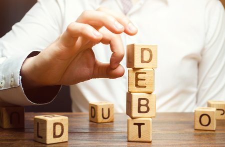 Biznesmen usuwa drewniane klocki z napisem Dług. Redukcja lub restrukturyzacja zadłużenia. Ogłoszenie upadłości. Odmowa spłaty długów lub pożyczek i ich unieważnienie. Zwolnienie z obsługi długów