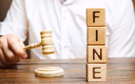 Wooden blocks with the word Fine and judge. Penalty as a punishment for a crime and offense. Financial punishment. Violations of traffic laws. Fraud. Fines can also be used as a form of tax Stock Photo
