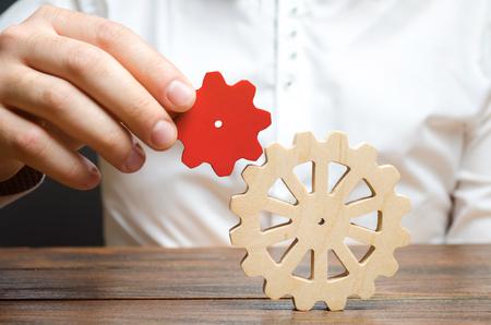 L'uomo d'affari collega un piccolo ingranaggio rosso a una grande ruota dentata. Simbolismo di stabilire processi aziendali e comunicazione. Aumenta l'efficienza e la produttività. La migliore formula aziendale per il successo