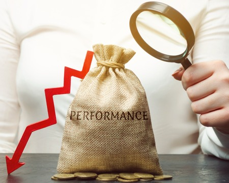 A woman holds a magnifying glass over a bag with the word Performance and an arrow down. The concept of low productivity and business profitability. Unprofitability. Bad investment. Bankruptcy