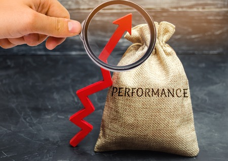 The magnifying glass is looking at the bag with the word Performance and the up arrow. The concept of improving business efficiency. A good result of the production activities of the working team