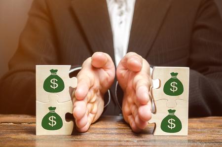 Geschäftsmann trennt das Holzpuzzle mit einem Bild von Geld. Das Konzept der Finanzverwaltung und Verteilung von Mitteln. Sparen und investieren. Eigentumsteilung. Scheidung und Rechtsberatung