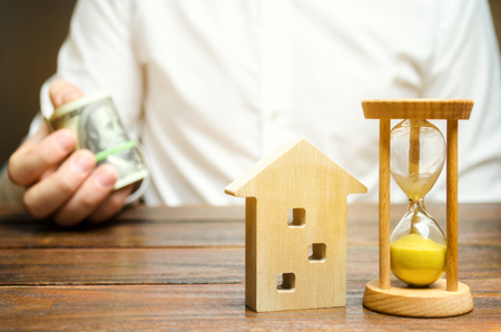 Wooden house and clock. Businessman holds money. Payment of deposit or advance payment for renting a home or apartment. Long-term mortgage on the house. Mortgage vacations. Buying and selling property 免版税图像 - 120634108