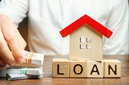 Wooden blocks with the word Loan, house and money in the hands of a businessman. The concept of buying an apartment or house in debt. Mortgage credit lending. Payment of interest rates. Saving money