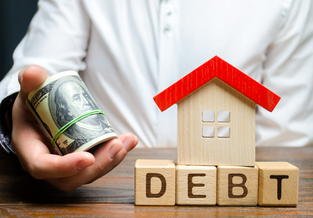 Wooden blocks with the word Debt, house and dollars in the hands of a businessman. The concept of timely payment of debt for real estate. Buying a property in debt. Mortgage. Credit for the apartment.