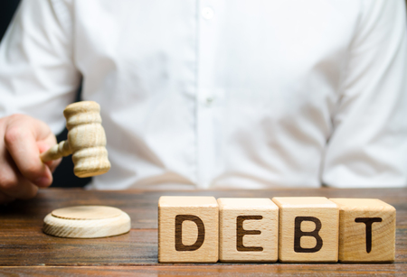 Wooden blocks with the word Debt and judge with a gavel. The concept of judicial punishment for non-payment of debt. Property debts. Tax evasion / avoidance. Bankruptcy and financial crisis 免版税图像