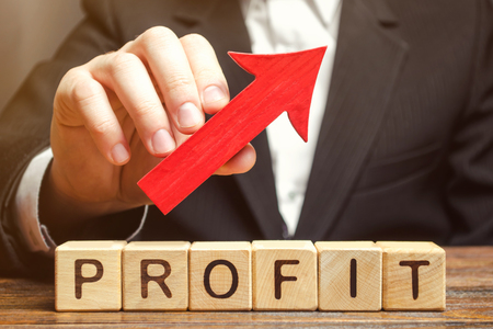 A businessman holds a red arrow up over wooden blocks with the word Profit. Successful business and high profits. Profitability. Revenue growth and capital accumulation. Performance rise Banque d'images